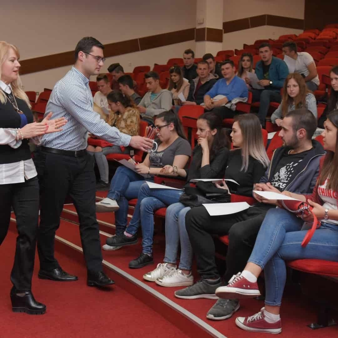 Students being given pencils at a presentation at the International Slavic University G. R. Derzhavin, while they are sitting on a red chairs.
