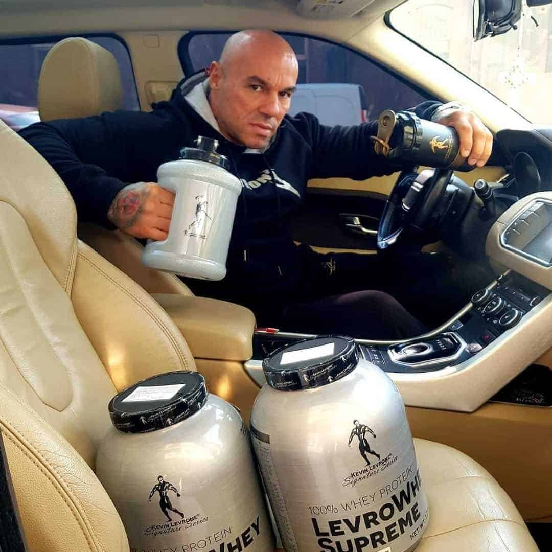 Tose Zafrov sitting in his car. He is wearing a black Levrone hoodie, and he is holding a product from the Levrone Signature Series in one of his hands. There are some products from the Levrone Signature Series in front of him.