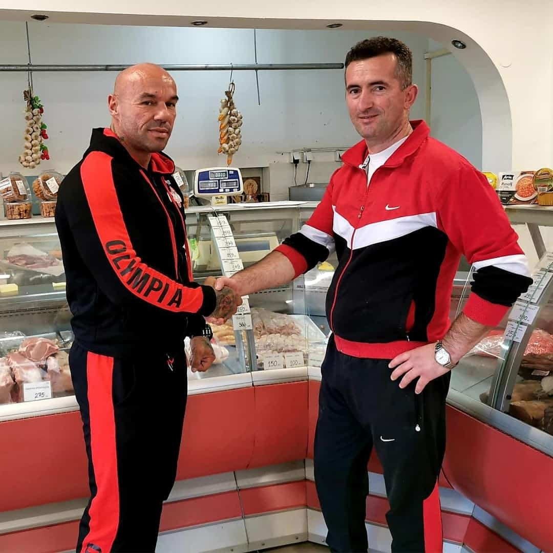 Tose Zafirov and the owner of Butcher Shop Ivanovski shaking their hands in the butcher shop. They are both wearing tracksuits in black colour, with red details.
