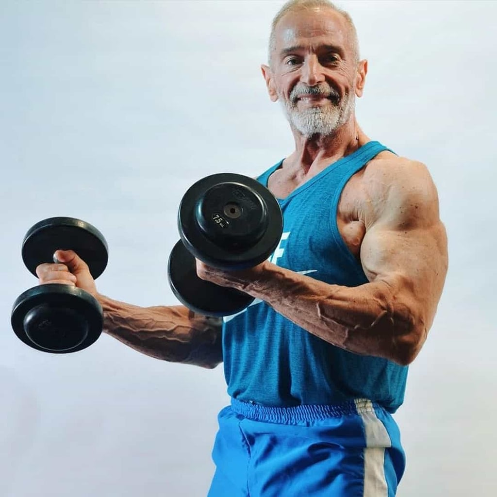 An image of Petar Celik using dumbbells to train his biceps at an older age while wearing a blue Nike shirt and blue shorts.