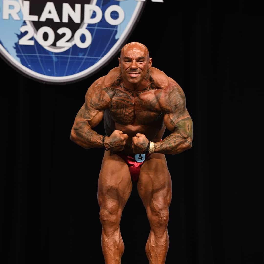 Tose Zafirov in a red trunks, flexing his muscles on the stage on Mr. Olympia Orlando 2020