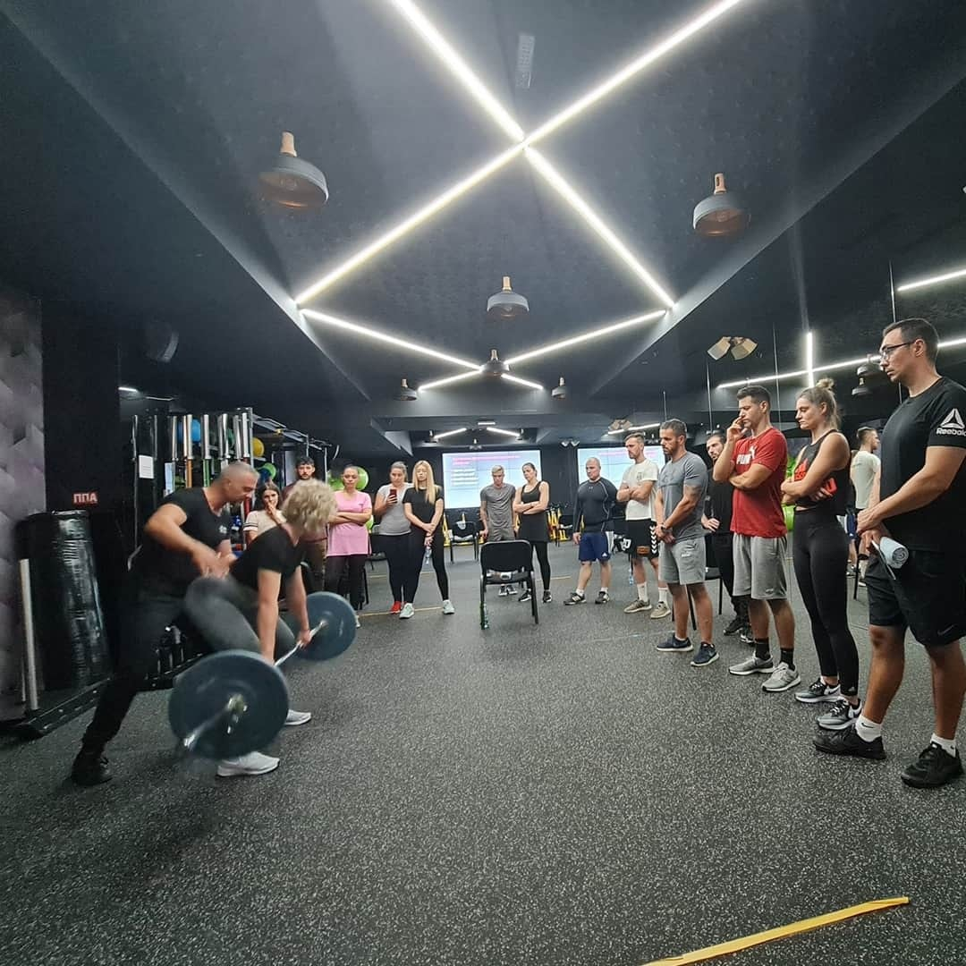 An exercise and practical example of what it is like to do deadlifts as showcased on the Fit Biz academy by an instructor. One girl is practicing with the instructor and the other s are looking at them.