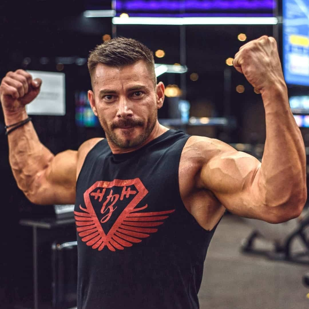 Trajche Stojanov flexing his hand's muscles and starting at the camera while wearing black t-shirt with red details.