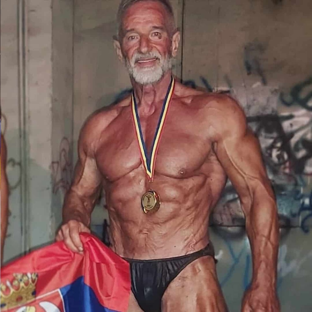 Petar Celik in a black trunks and without t-shirt, wearing a golden medal around his neck and smiling at the camera. He is holding the Serbian flag in one of his hands.