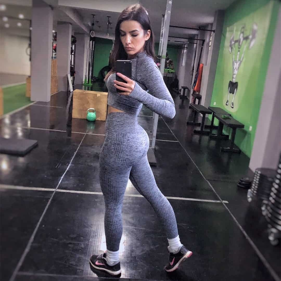 Emilija Mandzukovska taking an image of herself in the mirror while being at the gym. She is wearing grey sports set.