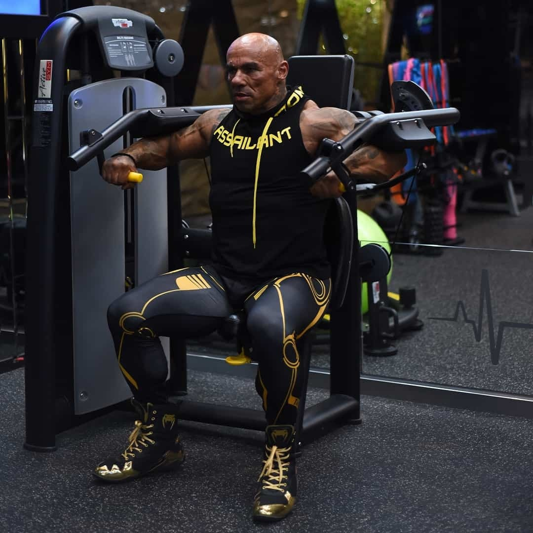 Tose Zafriov in a black t-shirt with hood, and black leggings, both with yellow details, doing exercise in the gym.