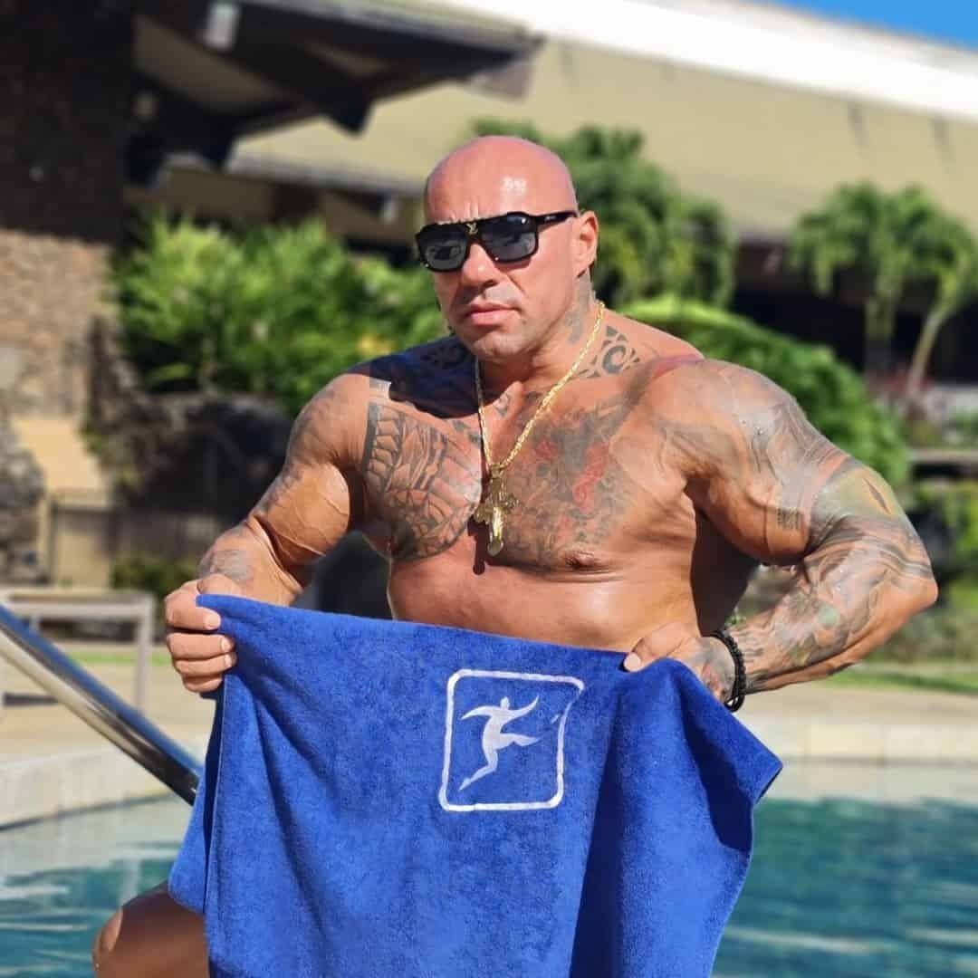 Tose Zafirov at the pool holding a Sport Life Towel in front of him, and wearing sunglasses.