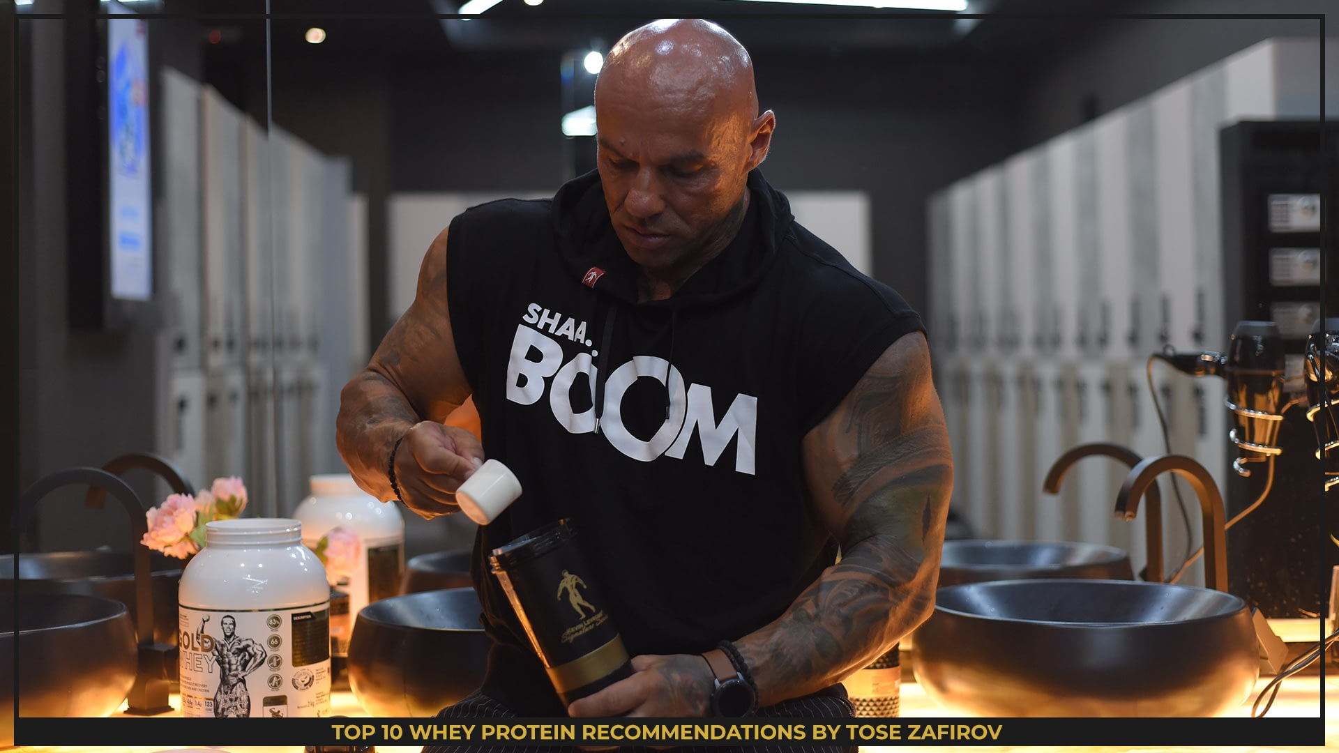 Tose Zafirov mixing a cup of Kevin Levrone Protein by the Gold Signature Series in a luxury bathroom, while wearing black shirt with ''BOOM'', white letters and a hood. There is a protein in the background.