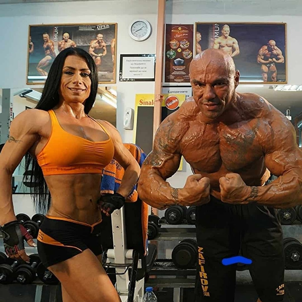 An image od Maria Bozinovska and Tose Zafirov, two professional bodybuilders. They are in the gym, flexing their muscles in front of the camera. Tose is shirtless with black sports shorts, and Maria wears an orange top with black shorts.