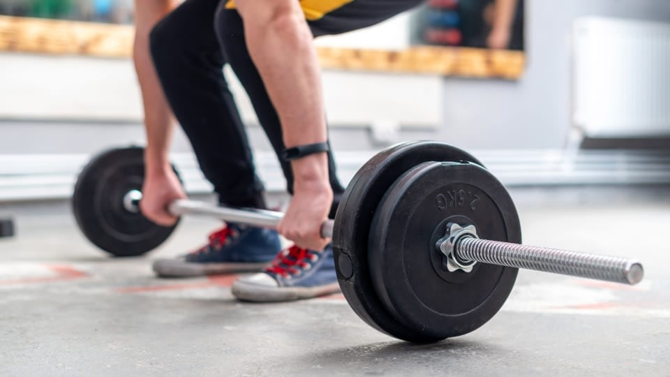A person about to lift weights. His face is not visible, the focus are his legs. He is wearing black sweatpants and blue sneakers with red shoelaces