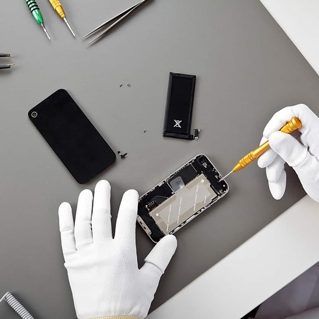An image of hands with white medical gloves, repairing an open smartphone