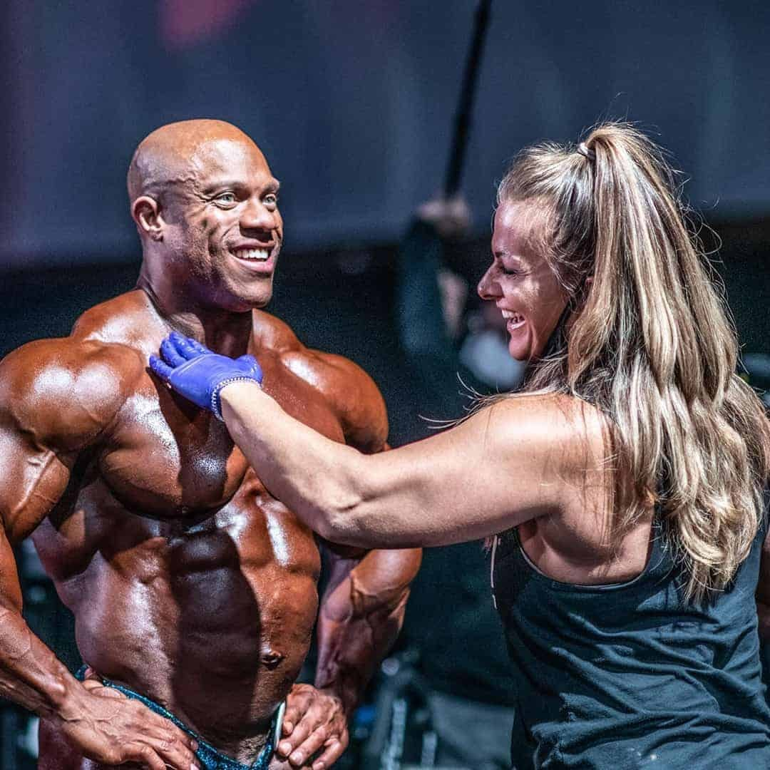 Phil Heath in the backstage on a competition, while one girl is putting some color on his body.