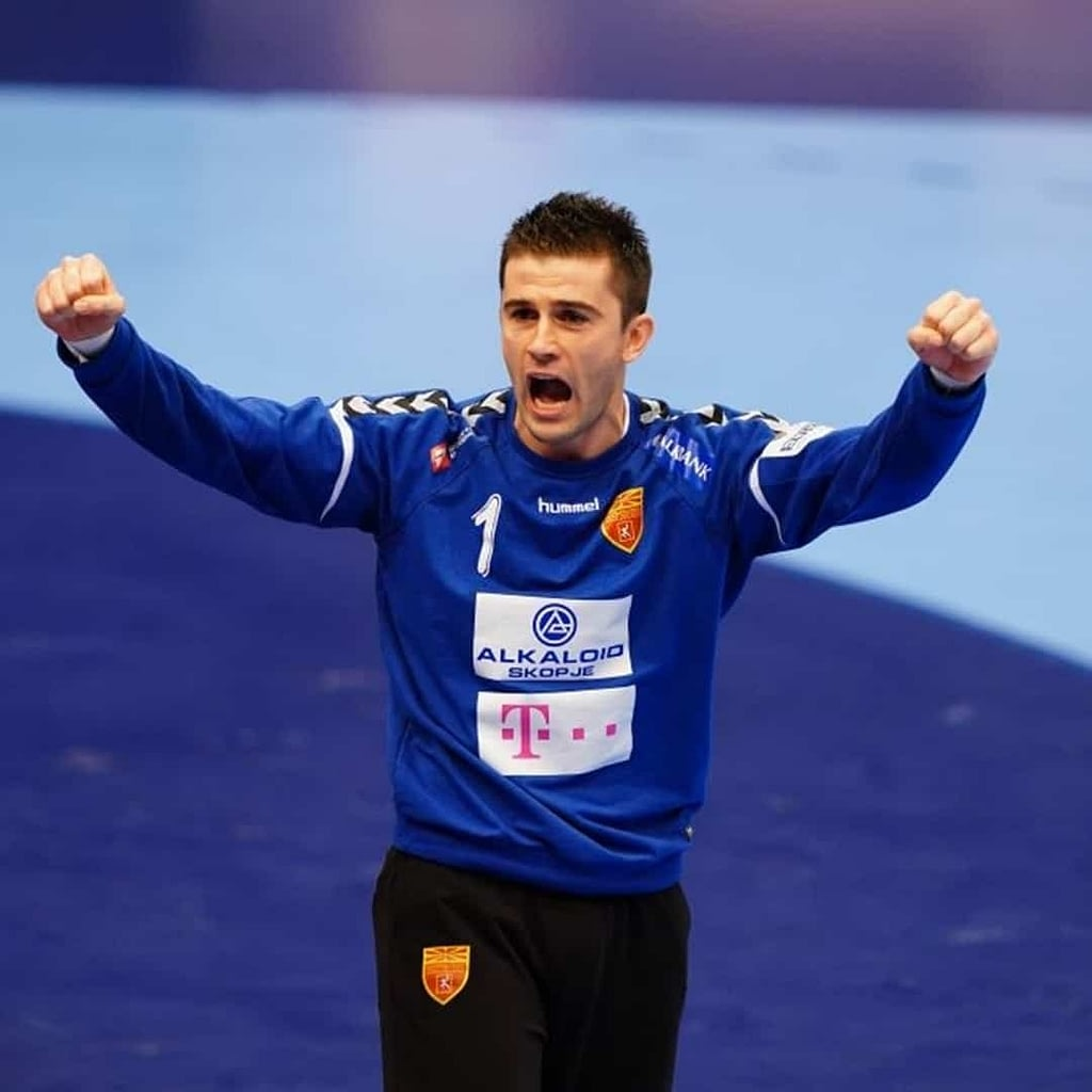 Nikola Mitrevski, with his hands in the air, and his mouth open. He is wearing navy blue blouse.