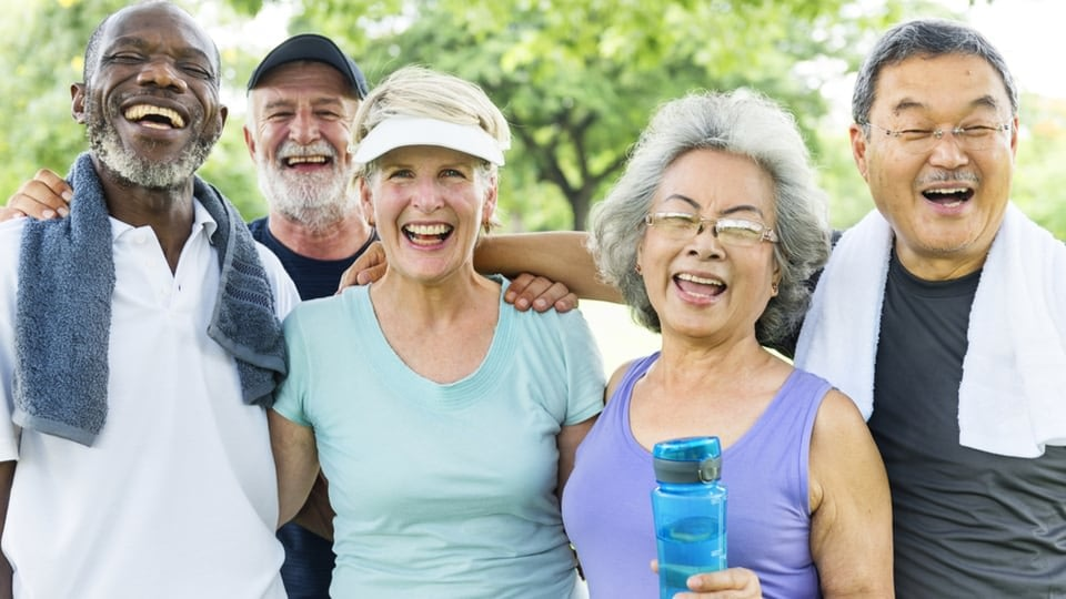 An image of elderly people, after their exercise. They are all smiling, and there are some trees in the background.