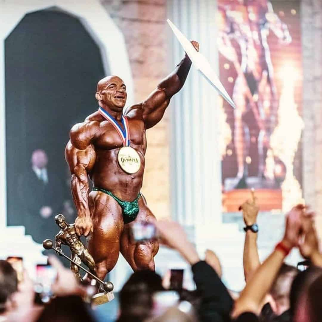 An image of Big Remy, on the Mr. Olympia Stage, with a medal on his neck, and a goblet in his hand. He is wearing dark green elegant trunks.