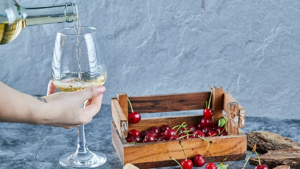 A hand holding a glass of wine and filling the glass from the bottle with the other one. There is also a wooden crate with cherries.