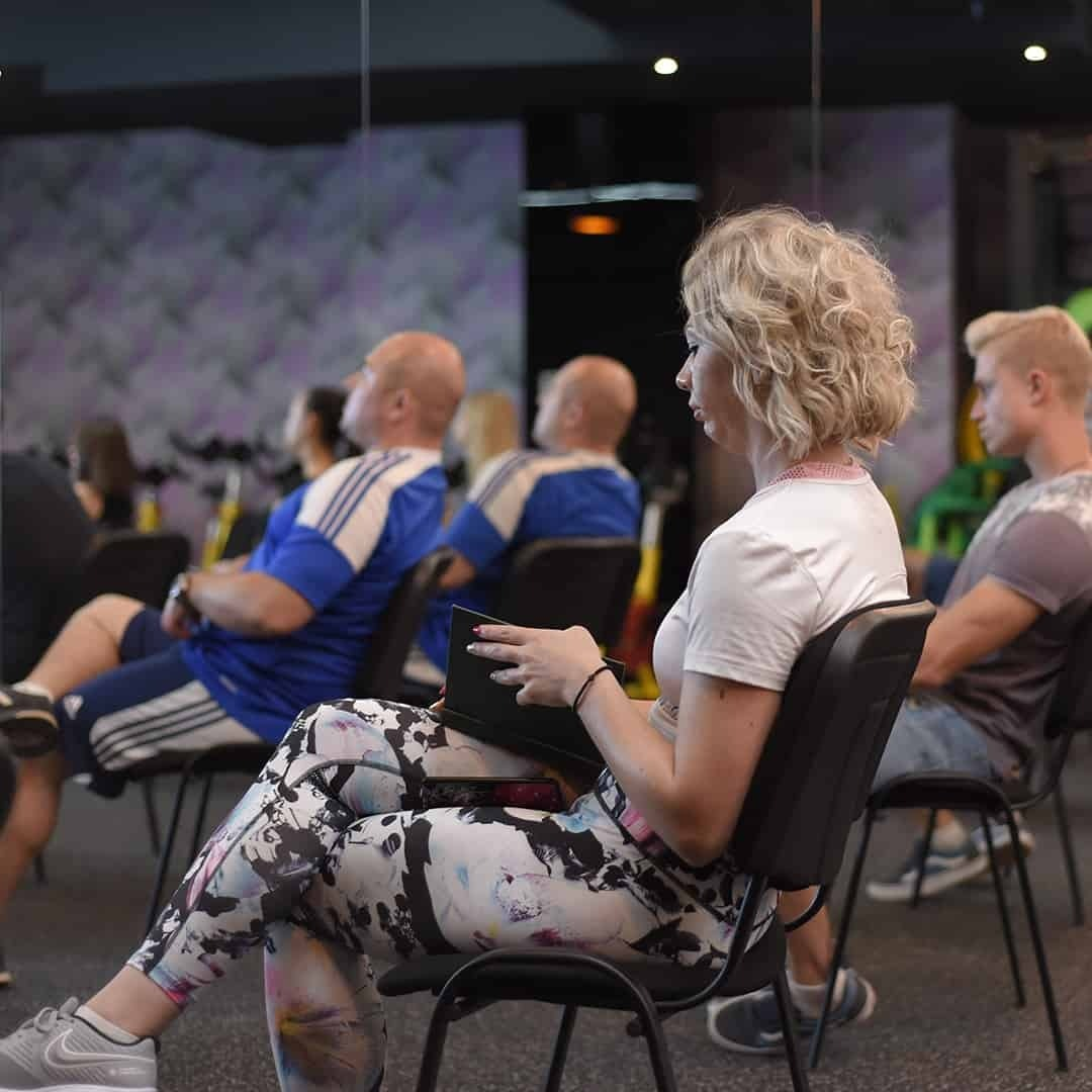An image of an attendee at the Fit Biz academy paying attention to the lecturers and reading up on the materials. She is sitting on a black chair with her legs crossed. The girl is wearing white t-shirt