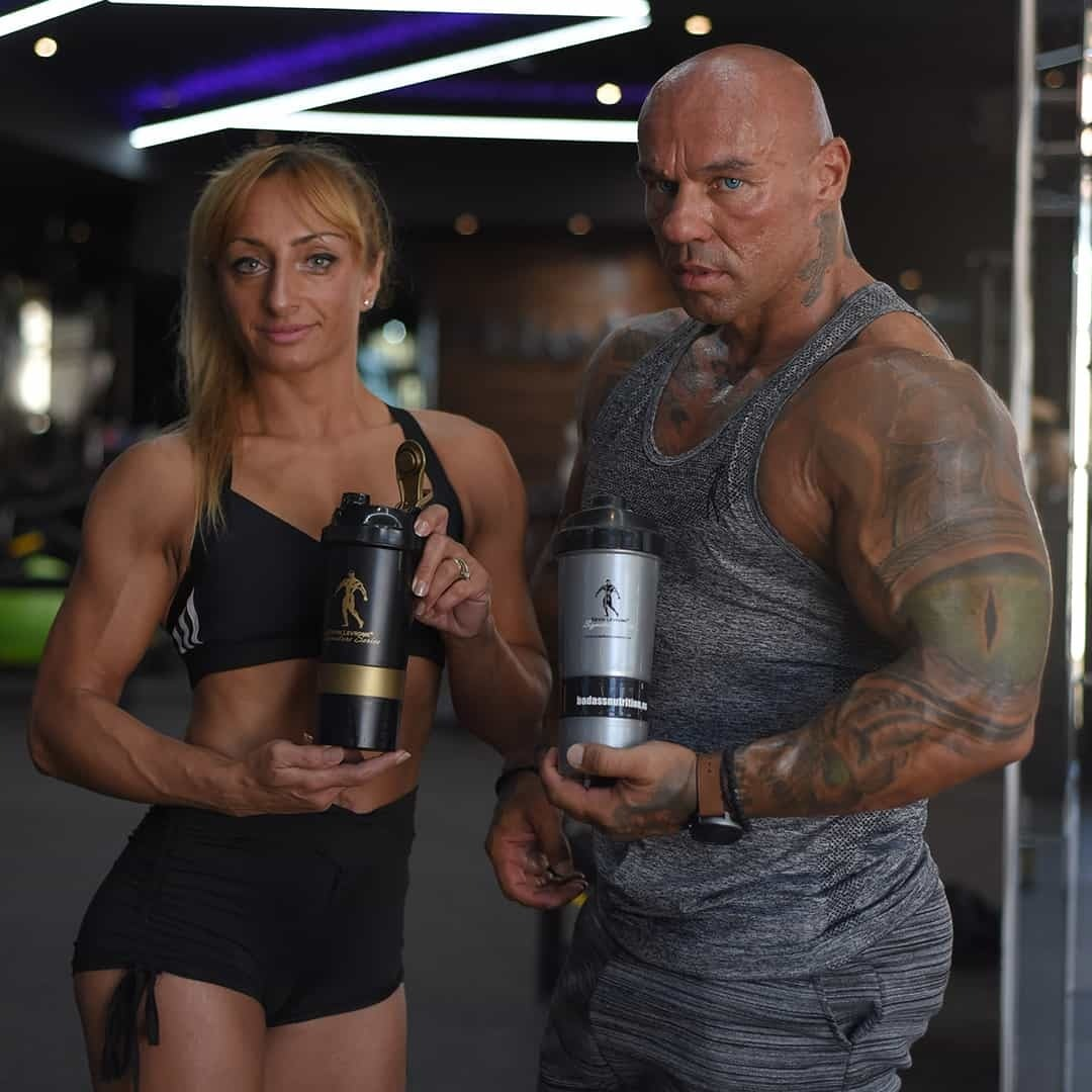 Tose Zafriov and Gabriela Zafriova in a gym, while holding shaker from the Levrone Signature Series. Gabriela is wearing black sports bra and short and Tose is wearing grey t-shirt and sweatpants.