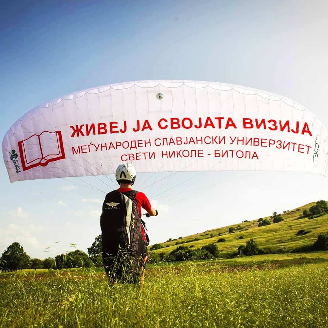 An image of a skydiver with the International Slavic University G. R. Derzhavin logo, with a hill in the background.
