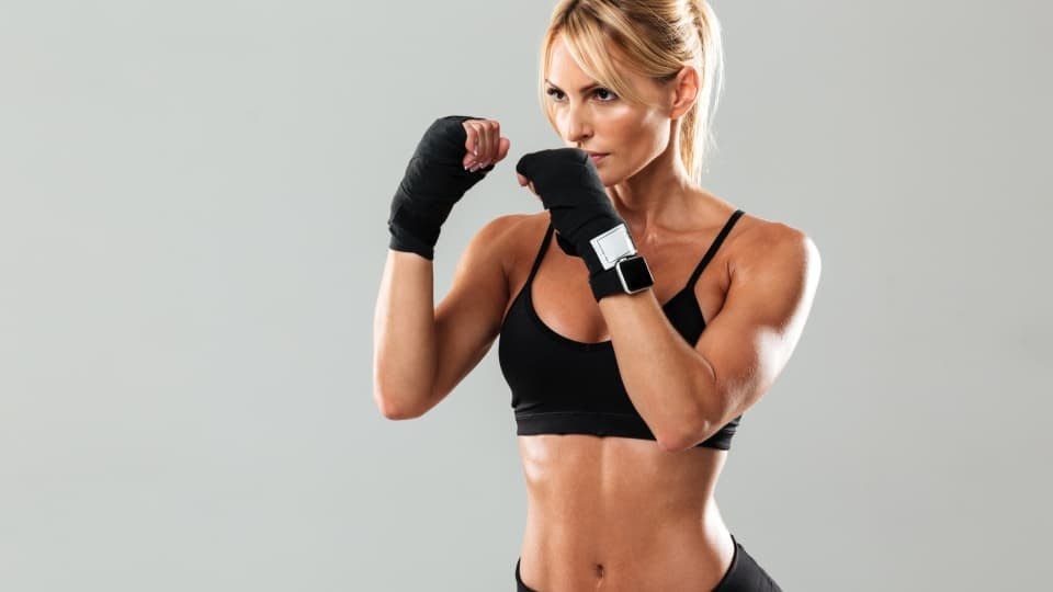 A woman engaging in kickboxing on light grey background. She is wearing black sports bra, sport gloves and black shorts.
