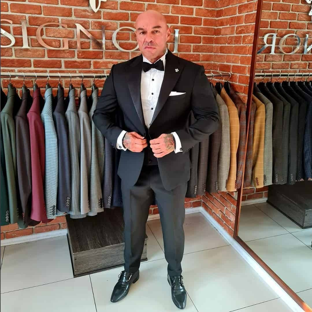 An image of Tose Zafirov wearing a black suit from Signori, a white shirt and a black bow tie, in their official store.