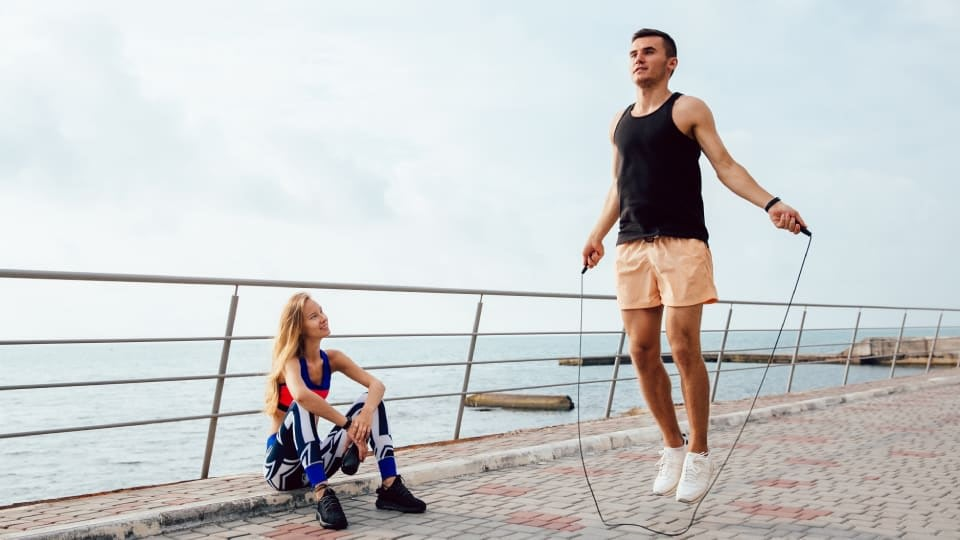 A man wearing black t-shirt and orange shorts is jumping rope next to the beach with a woman sitting and watching him. She is wearing sports bra and leggings in a black, red, blue and white colour.