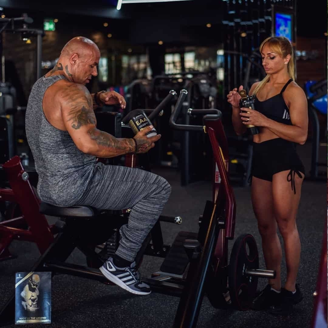 An image of Tose Zafirov and his wife Gabriela Zafirova about to drink EAA from Kevin Levrone Signature Series. Tose is wearing grey t-shirt and sweatpants and he is sitting on the gym equipment, while Gabriela is staying and watching the shaker.