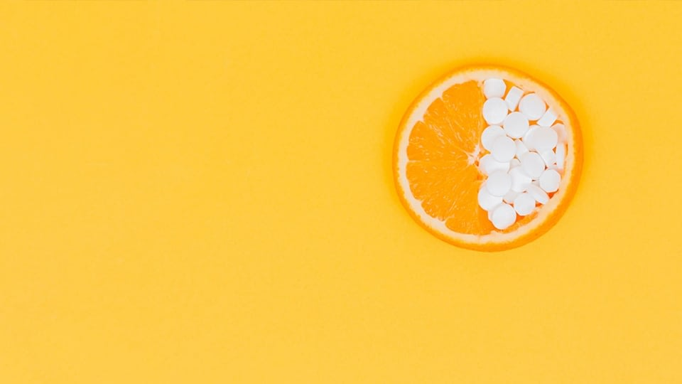 An image of an orange on a yellow backgound, there are Vitamin C pills on one half of the orange.