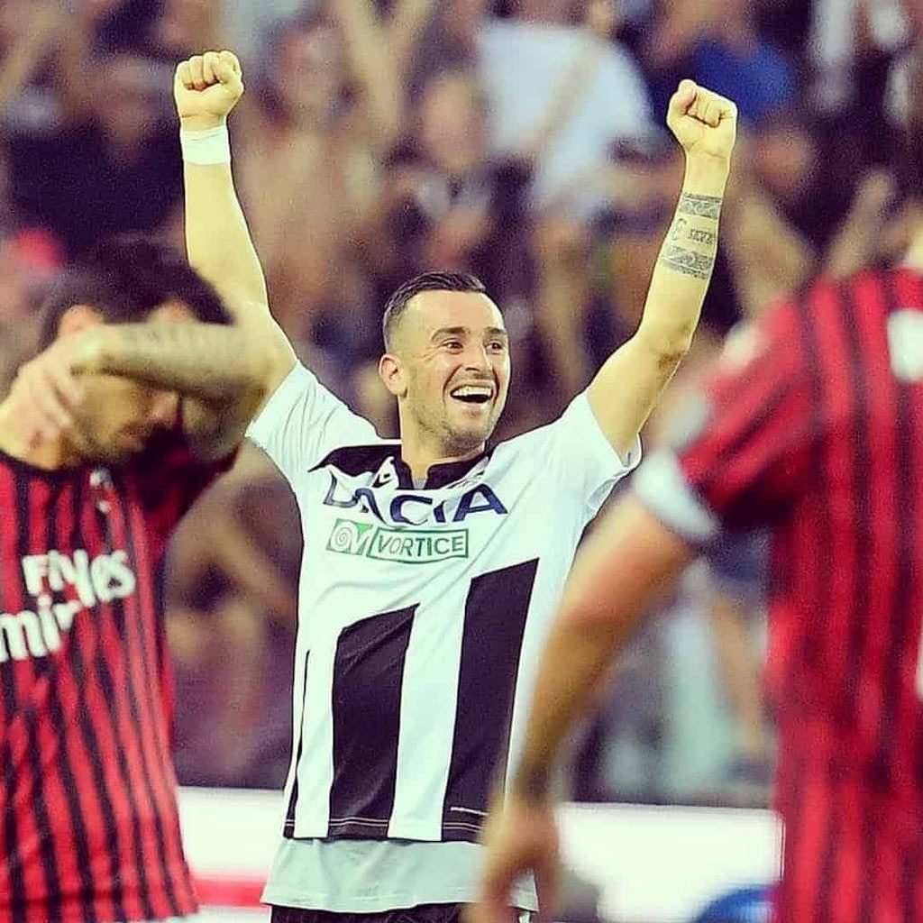 Ilija Nestorovski in a white jersey with black details, happy on the stadium with his hands up.