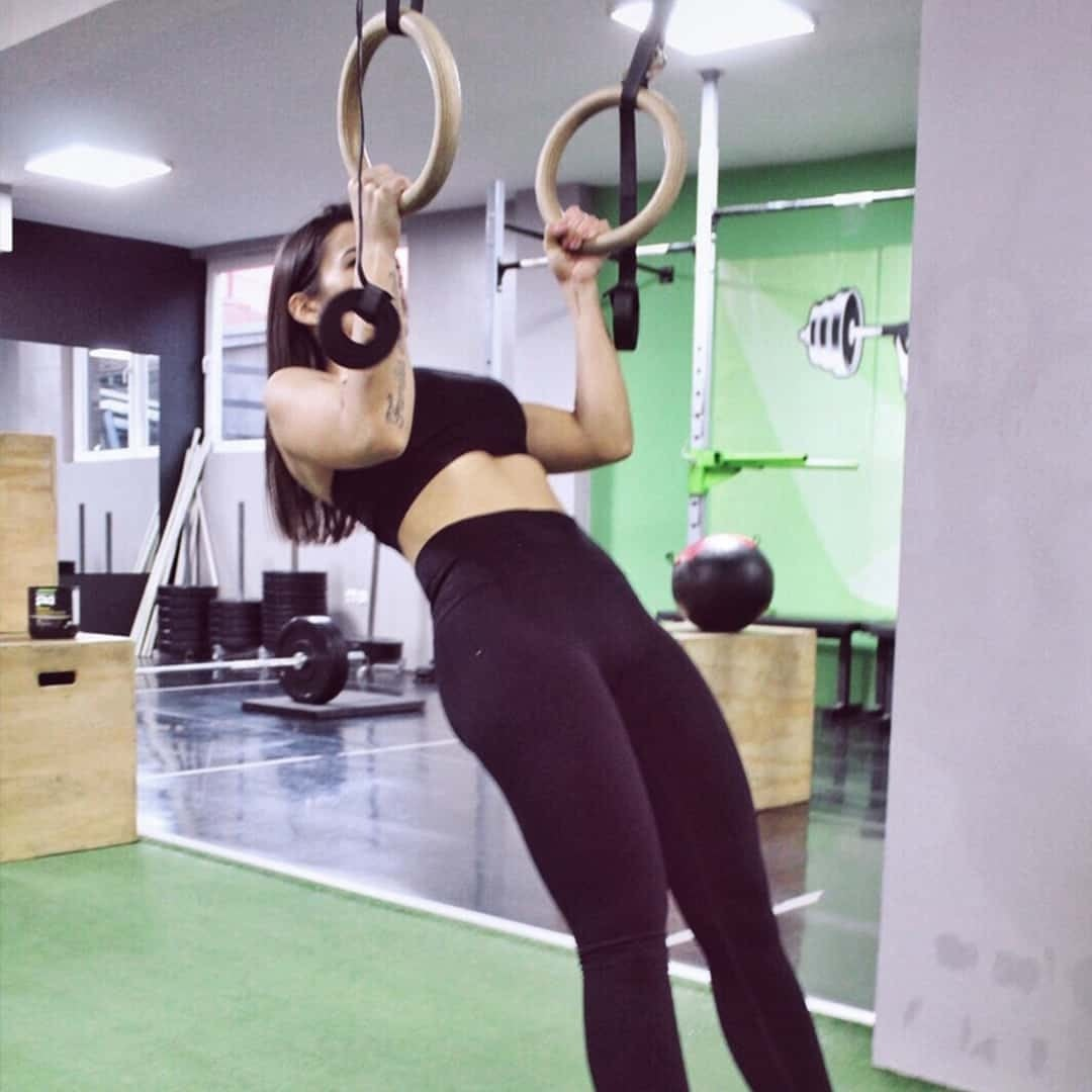 Emilija Mandzukovska training her body to the maximum at a local gym with gymnastic rings. She is wearing black sport bra and black leggings.