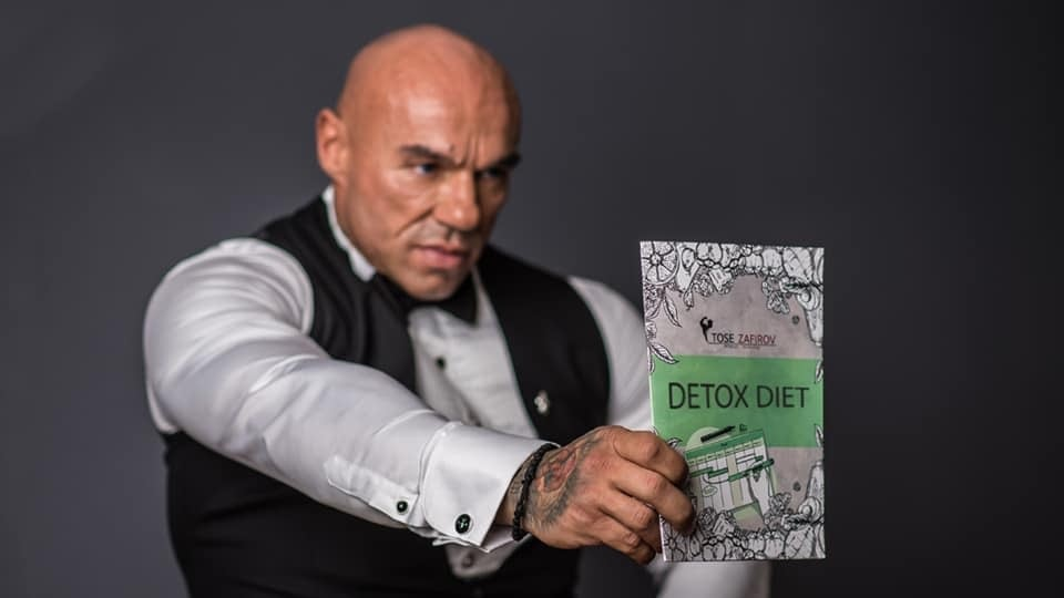 Tose Zafirov holding the Detox Diet straight at the camera while the Diet itself is in the main focus of the lens. He is not looking at the camera, and he is wearing white shirt, black elegant vest, and black bow tie from Signori
