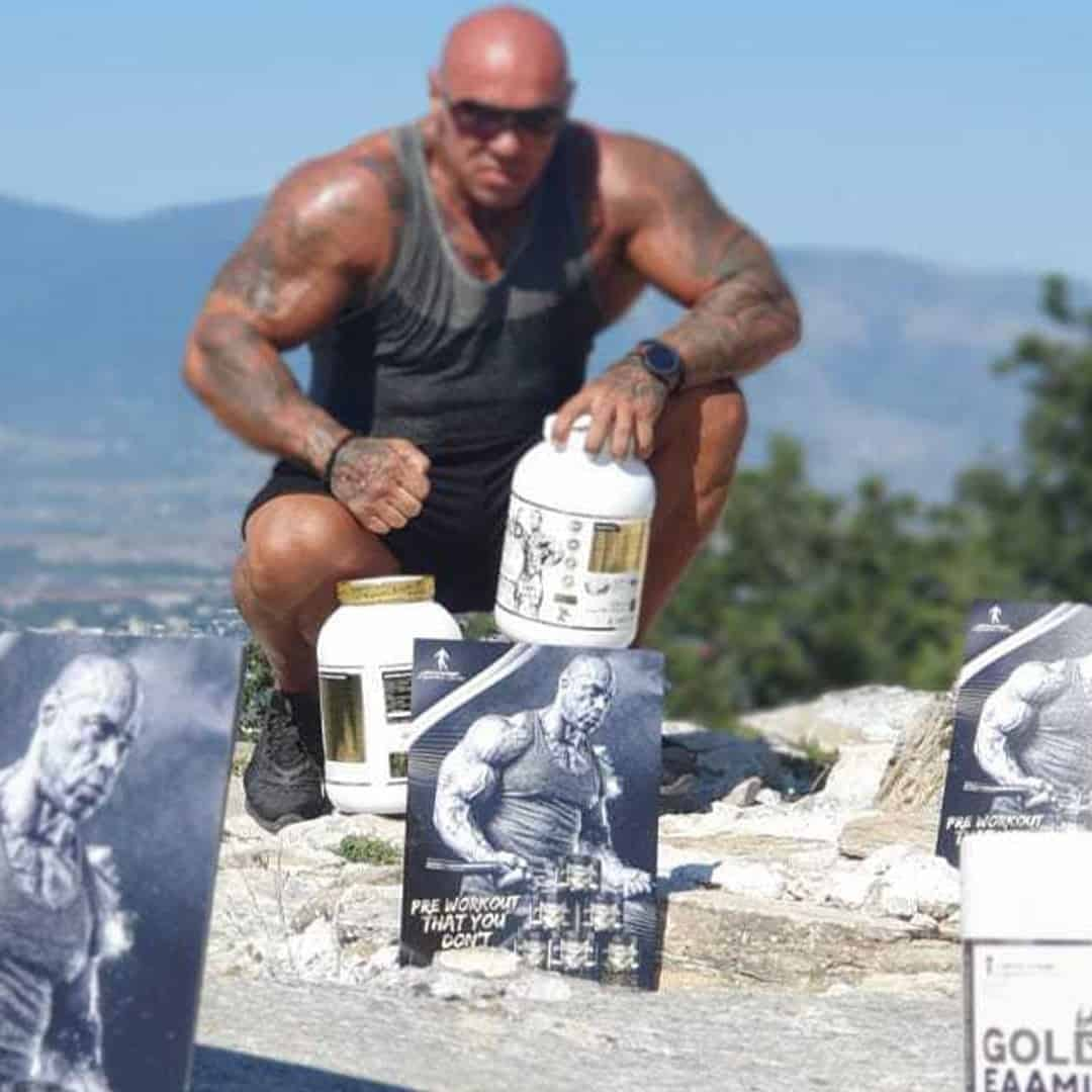Tose Zafirov on a mountain, in a grey t-shirt and sunglasses on his eyes, with some products from the Levrone gold line.