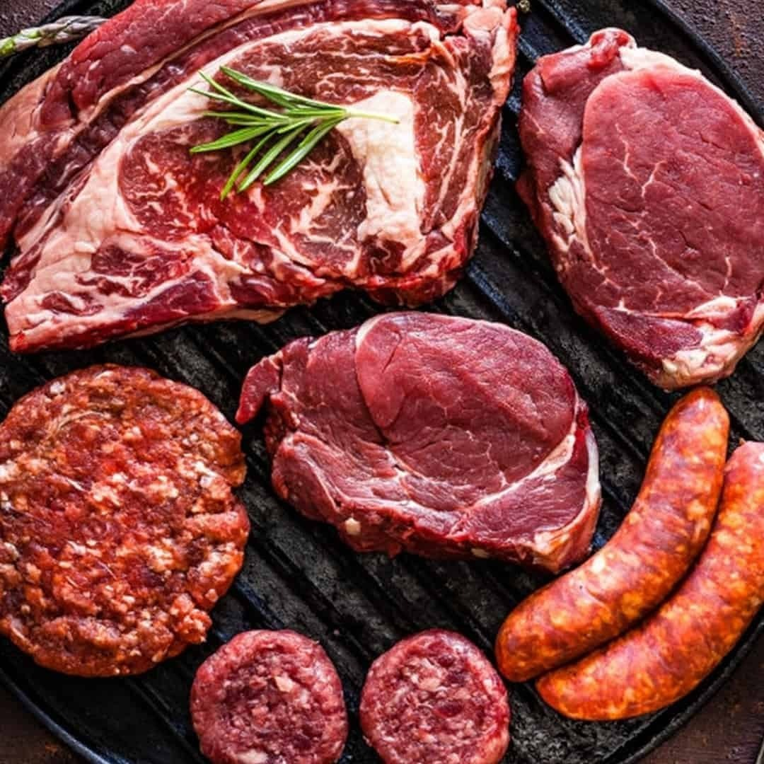 Different types of meat on a grill, beef, steak, and ground beef.