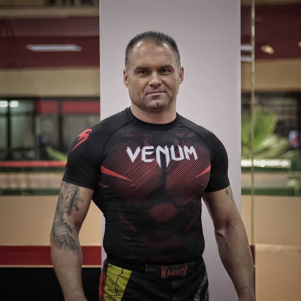 An image of Ivica Aleksovski. He is wearing black Venum, t-shirt with red details.