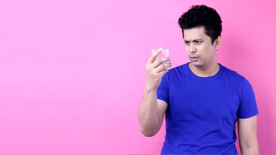 A person in a blue t-shirt, on a pink background staring into a cup of water.