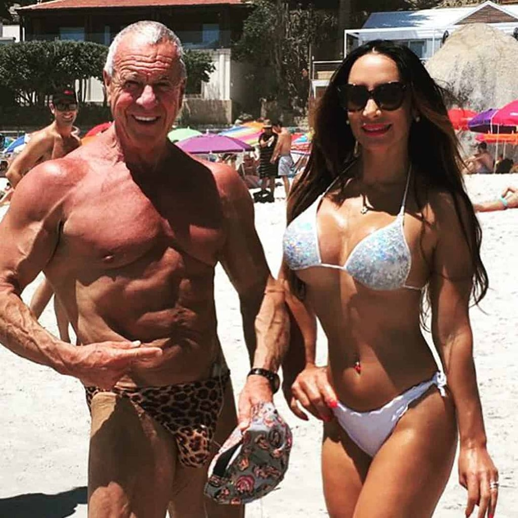 An image of Angelina Friedland and her husbnad Dion Friedland on the bach. Angelina is wearing white bikini set and sunglases on her eyes, and he is wearing leopard trunks. They are both smiling.