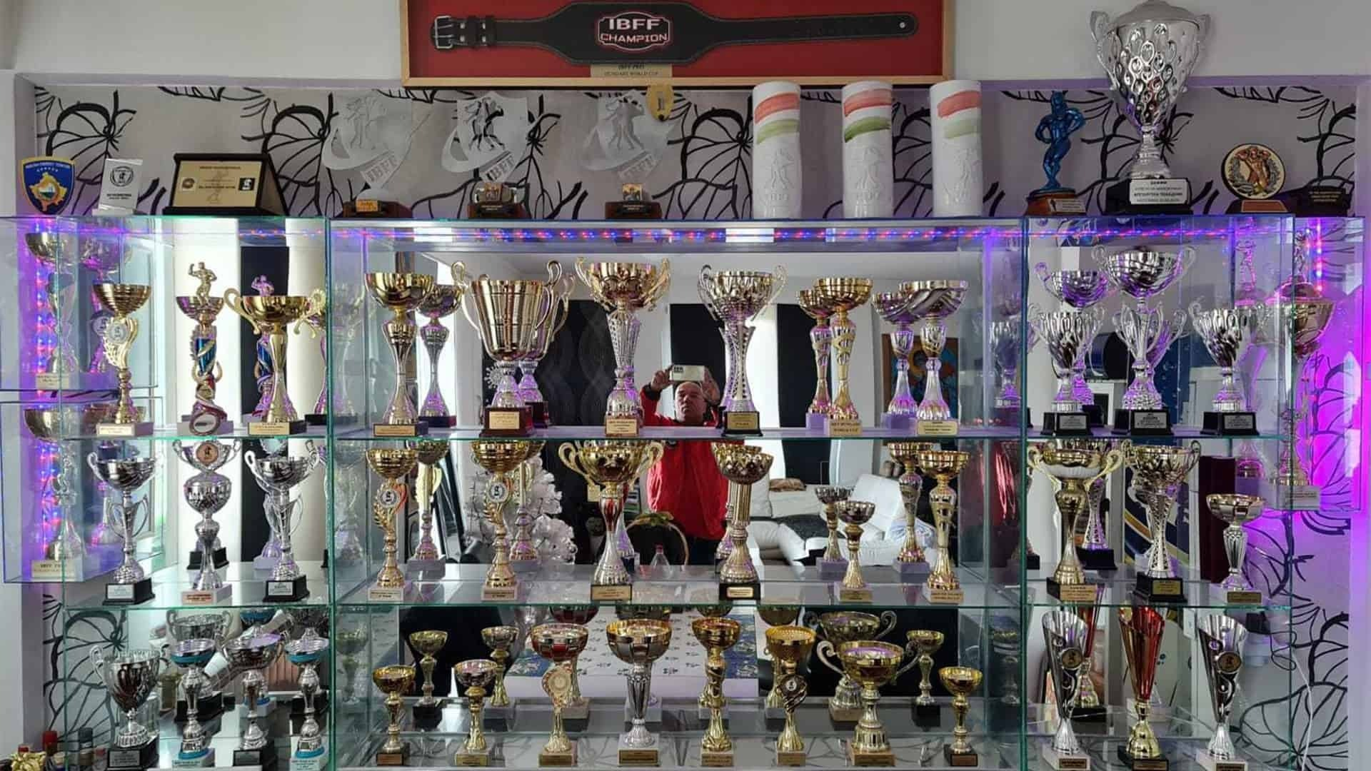 The trophies Tose Zafirov has acquired and won throughout the years, on a shell in his house, with a mirror behind them.