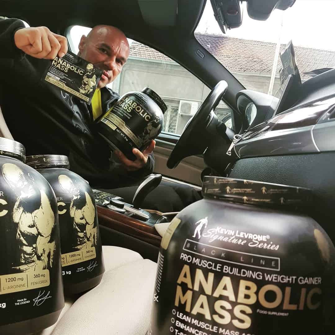 Tose Zafriov sitting in his car, with some products from Levrone Signature Series in his hands and next to him.