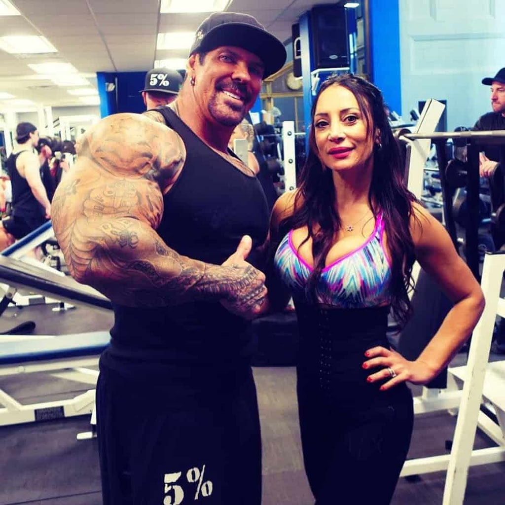 An image from Angelina Friedland and Rich Pianio. Thety are standing one to another in the gym. Angelina is wearing colorful sports bra and black leggings and Rich is wearing black cap, t-shirt and shorts.