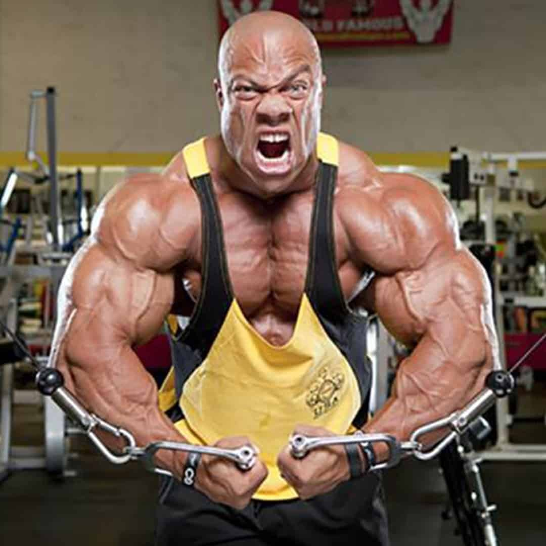 An image of Phil Heath in the gym, during his training. He is wearing yellow t-shirt with black details and he is yelling.