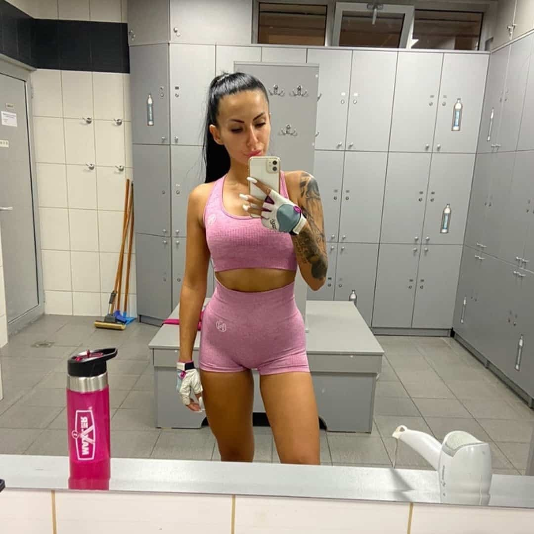 Viktorija Zajkova taking an image of herself in the mirror at a locker room at the gym where she is wearing pink training clothes.