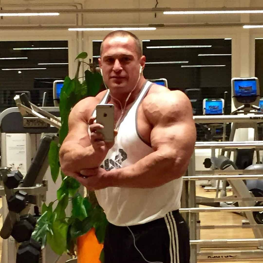 Ljubivoj Bakic at the gym taking a selfie, in front of a mirror, while flexing his muscles and wearing a white t-shirt.