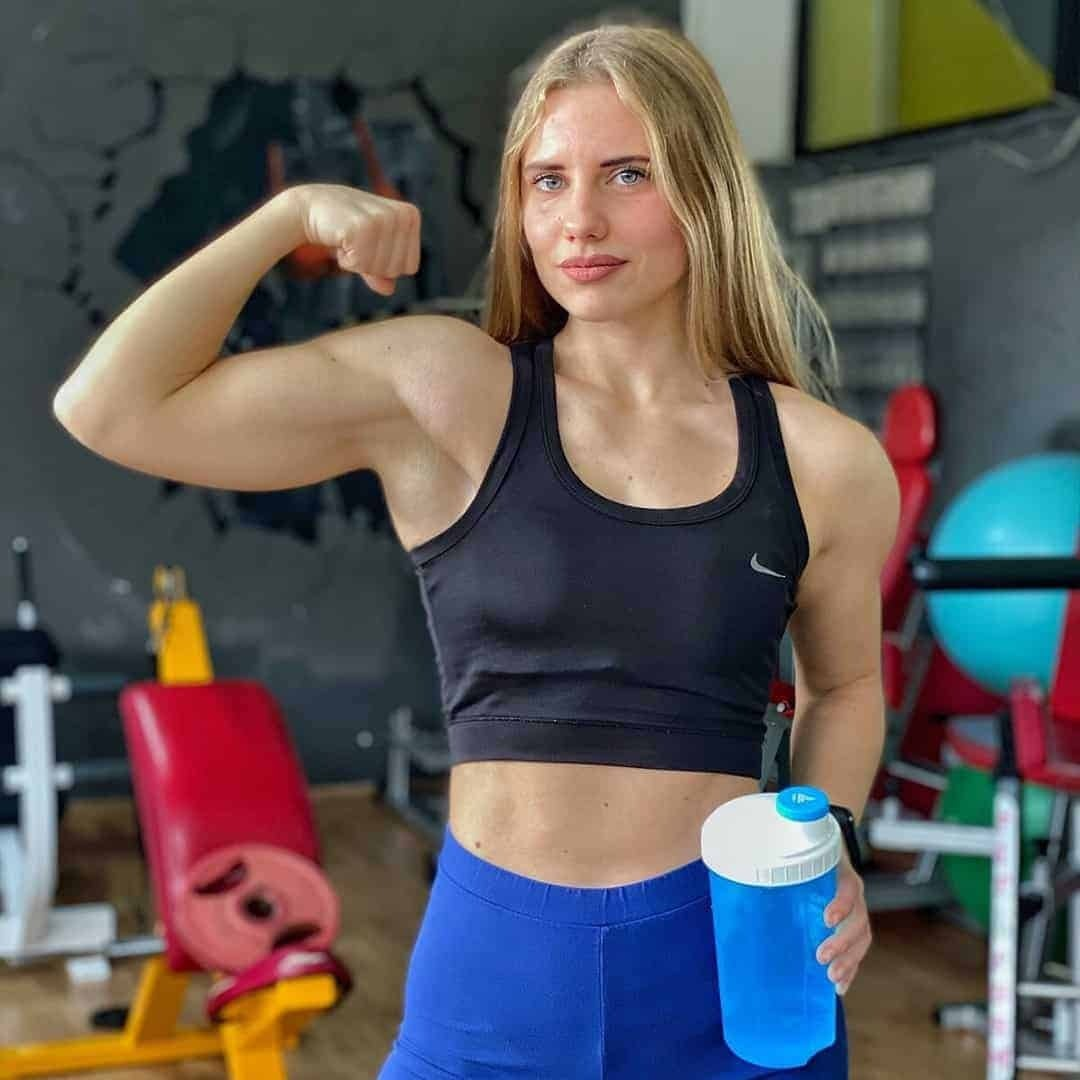 Sara Stojanoska flexing her biceps at the gym and staring at the camera, while holding blue bottle. She is wearing navy blue, sports bra, and blue leggings.