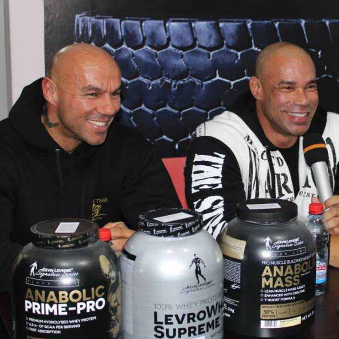 Tose Zafirov and Kevin Levrone on a press. There are some products from the black line and levrone signature series, in front of them. They are both smiling.