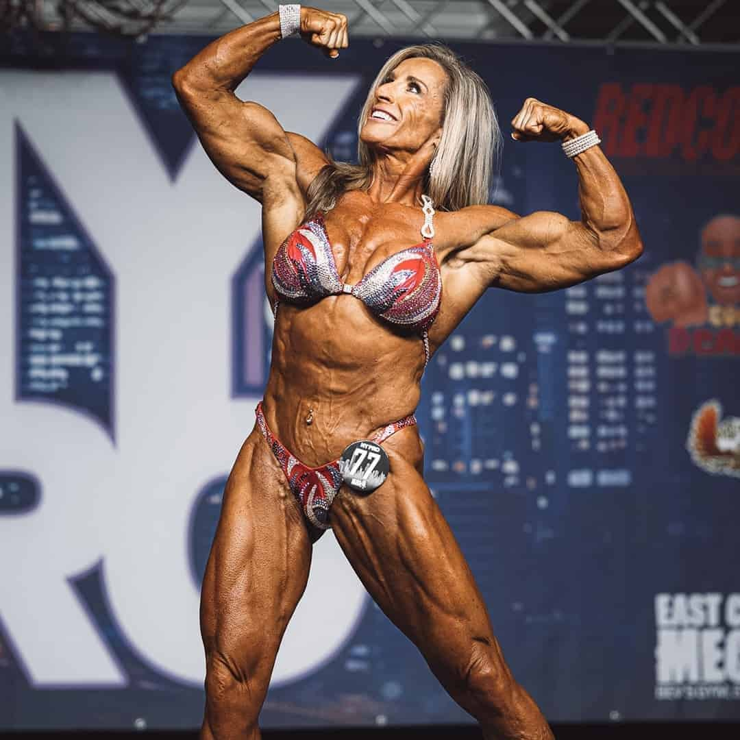 An image of a women, standing on the Mr. Olympia Stage while flexing her muscles. She is wearing elegant red bikini, with silver details, with number 77 on it.