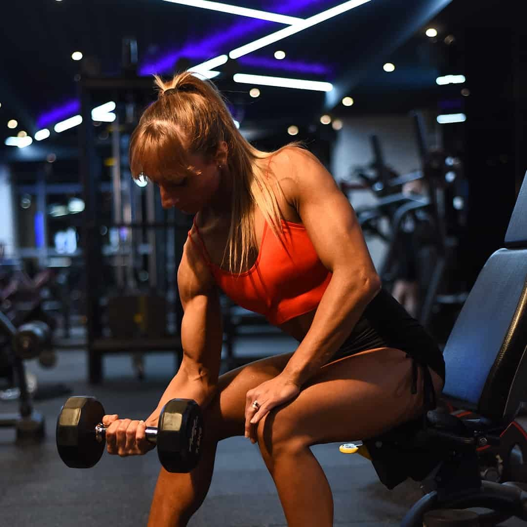 Gabriela Zafirova training her biceps with dumbbells, while siting on the gym equipment. She is wearing orange sports bra and black shorts.