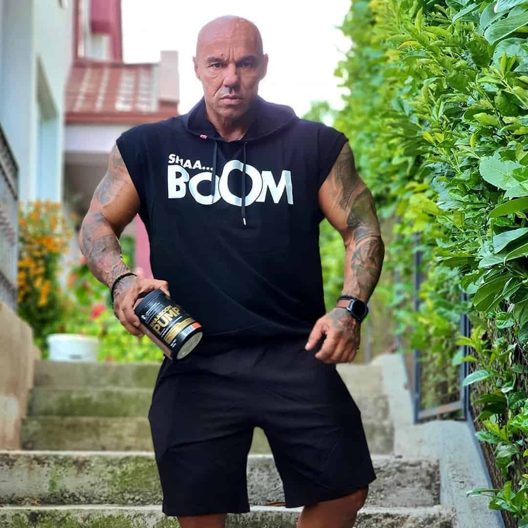 Tose Zafirov in a black Shaa-boom t-shirt, and black shorts. He is outdoor and he is holding Shaa-boom pump in his hands.
