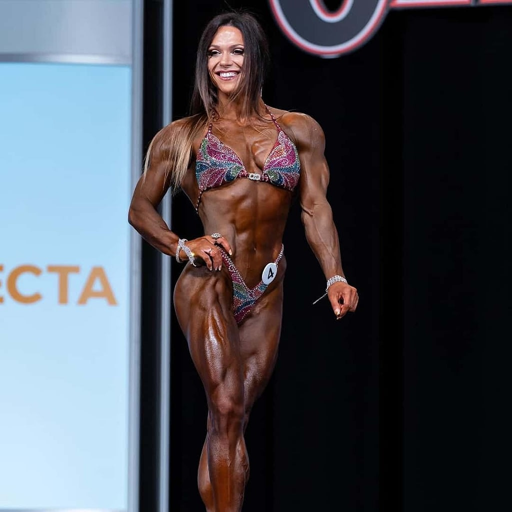 Oksana Grishina on stage flexing her muscles at the Mr. Olympia Competition. She is wearing elegant bikini
