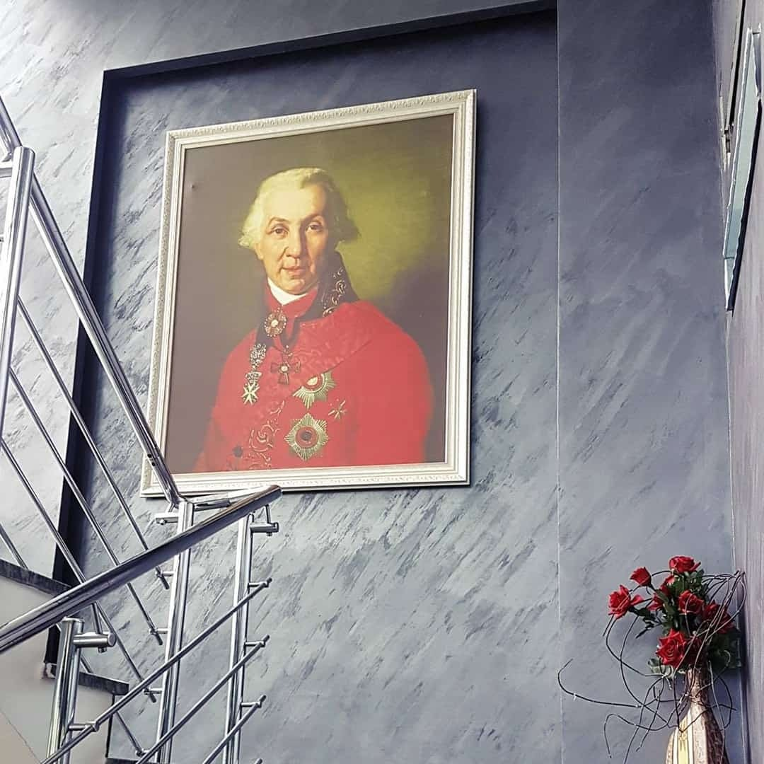 An image of the person behind International Slavic University G. R. Derzhavin on a grey wall, next to stairs. There are some red flowers in the corner too.