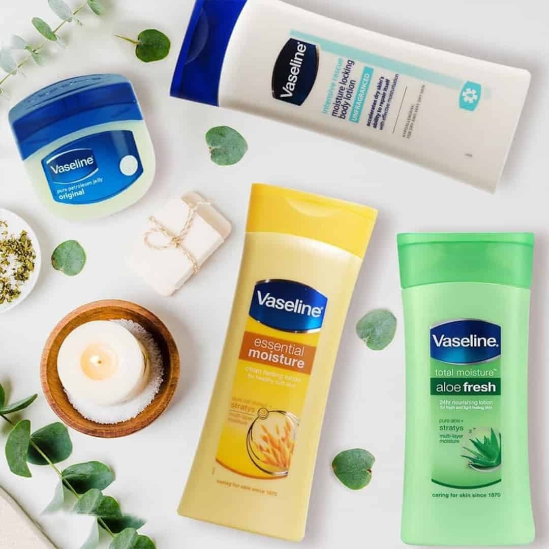 Vaseline Products on a white background, with a white candle next to them.